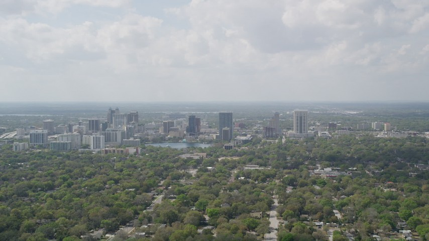 5K stock footage aerial video fly over trees toward Downtown Orlando and Lake Eola, Florida Aerial Stock Footage | AX0034_084