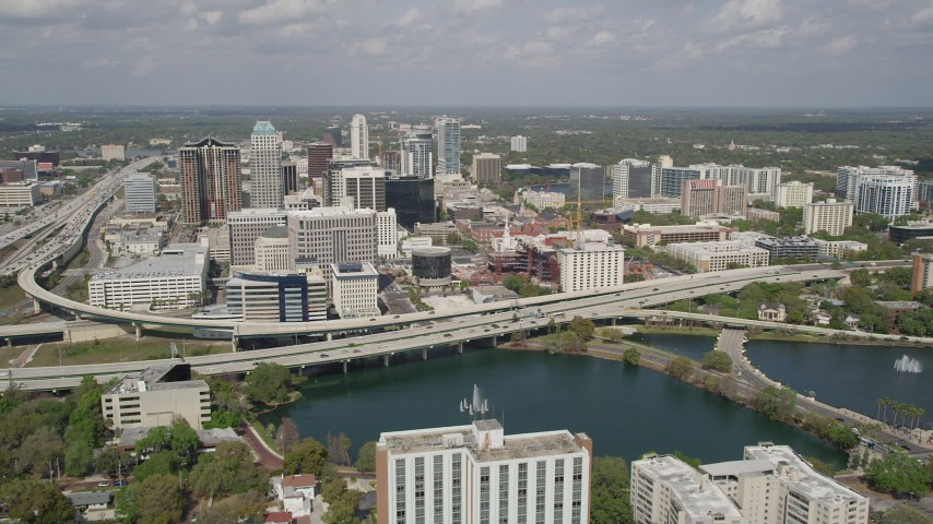 5K stock footage aerial video of orbiting Lake Lucerne revealing Downtown Orlando and the Expressway, Florida Aerial Stock Footage | AX0034_092