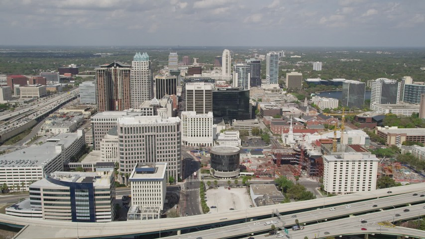 5K stock footage aerial video of flying over Downtown Orlando buildings following Orange Avenue, Florida Aerial Stock Footage | AX0034_093