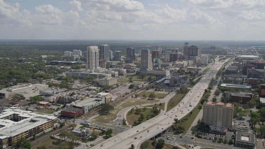 5K stock footage aerial video fly over Interstate 4 toward office buildings in Downtown Orlando, Florida Aerial Stock Footage | AX0034_099