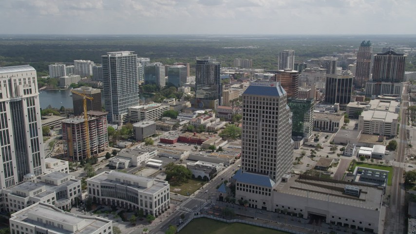 5K stock footage aerial video of flying over Downtown Orlando office buildings toward high-rises, Florida Aerial Stock Footage | AX0034_100