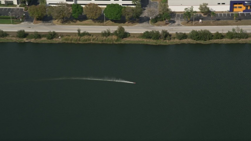 5K stock footage aerial video of tracking a toy speedboat racing around in a pond, Orlando, Florida Aerial Stock Footage | AX0035_010E