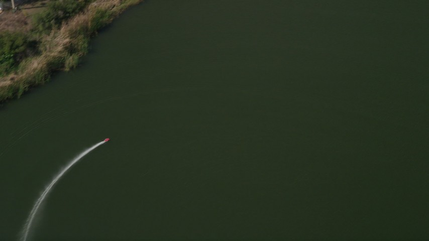 5K stock footage aerial video of tracking a toy speedboat racing across a pond, Orlando, Florida Aerial Stock Footage   AX0035_011