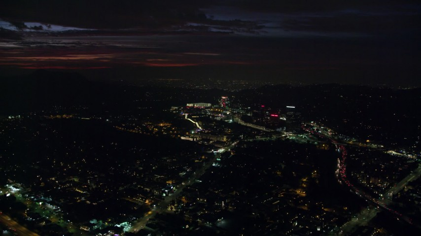 8K stock footage aerial video approaching Universal Studios Hollywood in Universal City at night in California Aerial Stock Footage | AX0156_004