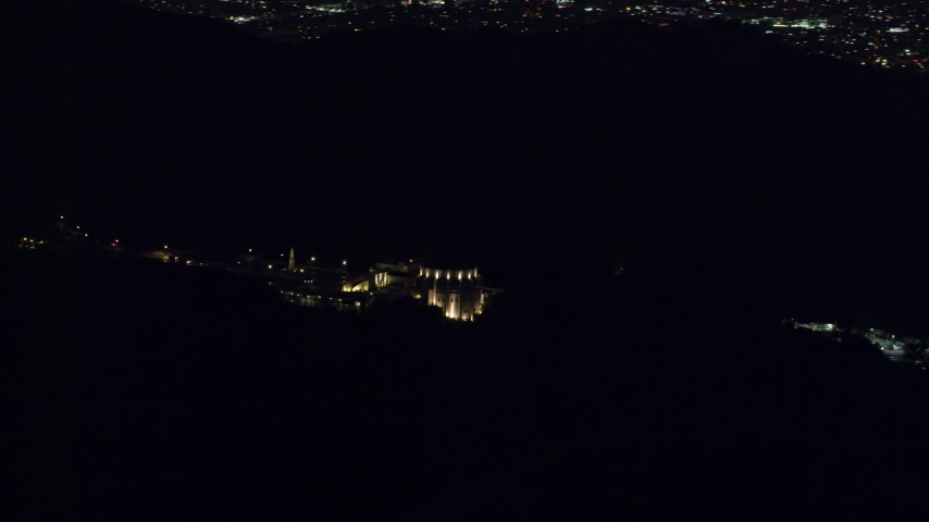 8K stock footage aerial video rounding the Griffith Observatory in the hills at night in Los Angeles, California Aerial Stock Footage | AX0156_008