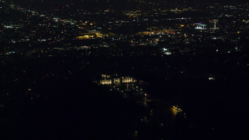 8K stock footage aerial video orbiting the Griffith Observatory at night with a view of Hollywood in Los Angeles, California Aerial Stock Footage | AX0156_011
