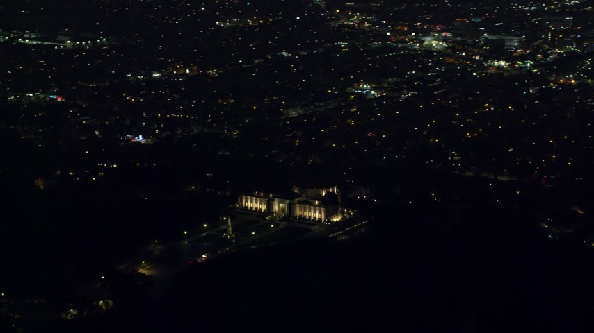 8K stock footage aerial video orbiting the Griffith Observatory at night with a view of Hollywood in Los Angeles, California Aerial Stock Footage | AX0156_012
