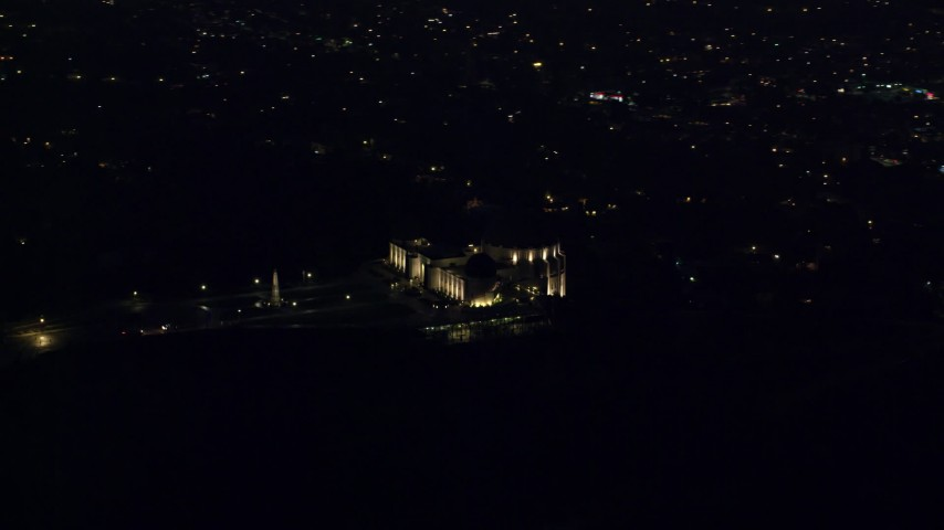 8K stock footage aerial video of the hilltop Griffith Observatory at night with a view of Hollywood in Los Angeles, California Aerial Stock Footage | AX0156_013
