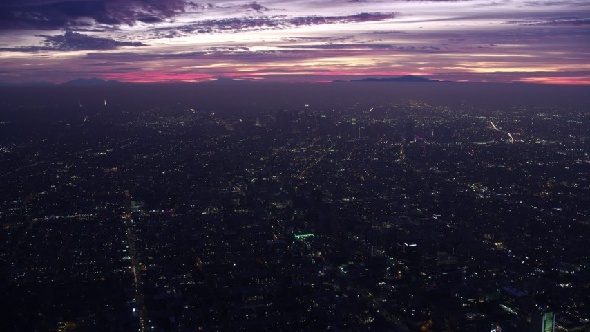 8K stock footage aerial video flying over the city toward Downtown Los Angeles skyscrapers at sunrise, California Aerial Stock Footage | AX0156_031