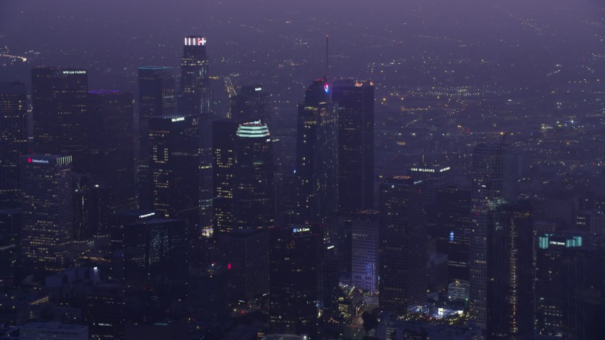 8K stock footage aerial video of a reverse view of skyscrapers in Downtown Los Angeles at sunrise, California Aerial Stock Footage | AX0156_038