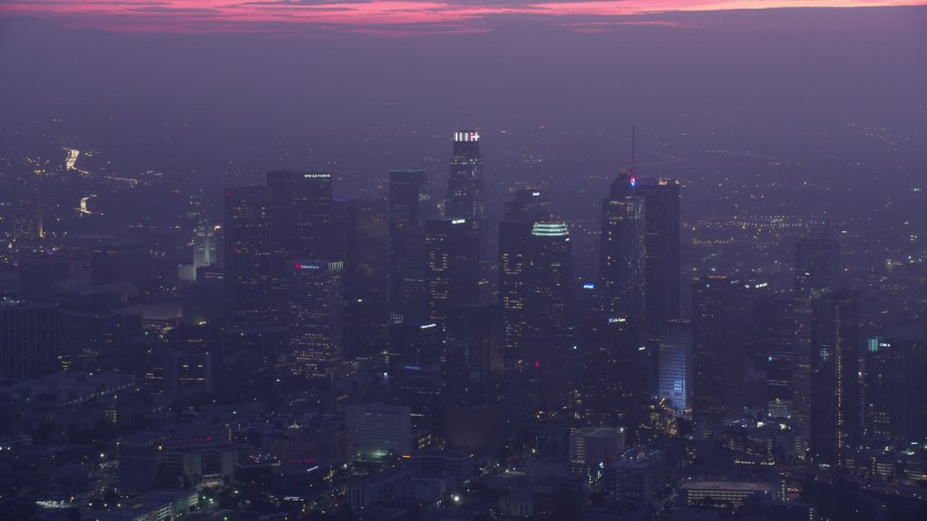 8K stock footage aerial video of a reverse view of tall skyscrapers in Downtown Los Angeles at sunrise, California Aerial Stock Footage | AX0156_039