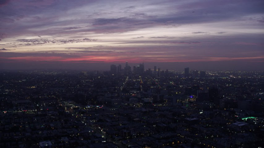 8K stock footage aerial video flying across the city to approach Downtown Los Angeles skyline at sunrise, California Aerial Stock Footage | AX0156_041