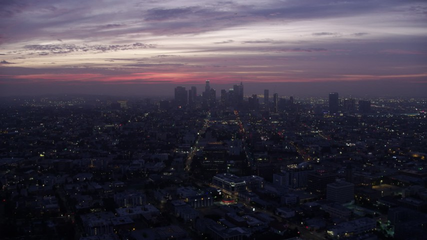 8K stock footage aerial video flying across the city toward Downtown Los Angeles skyline at sunrise, California Aerial Stock Footage | AX0156_042