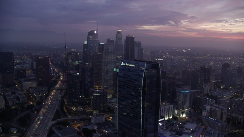 8K stock footage aerial video of a reverse view of the Wilshire Grand Center in Downtown Los Angeles at sunrise, California, reveal the Ritz-Carlton Aerial Stock Footage | AX0156_050