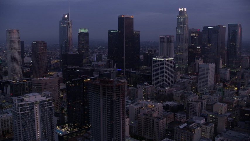 8K stock footage aerial video passing by tall skyscrapers in Downtown Los Angeles at sunrise, California Aerial Stock Footage | AX0156_052