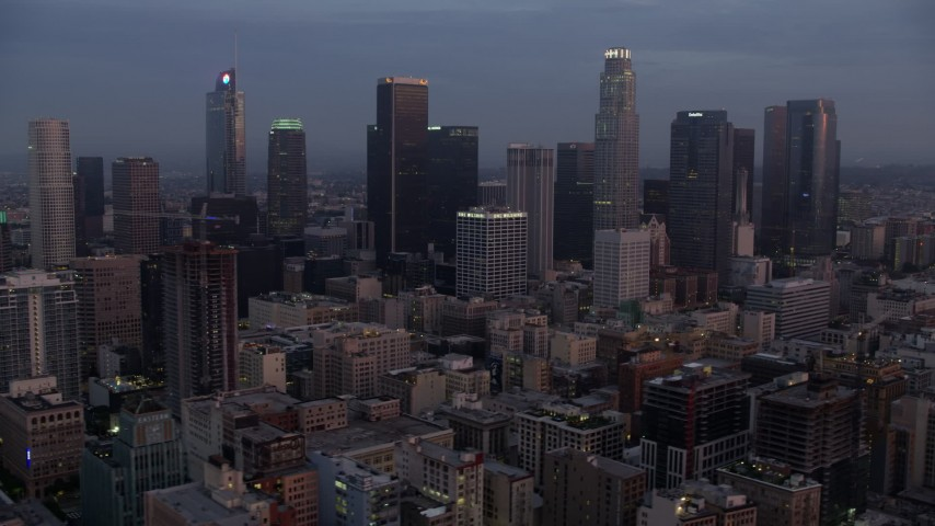 8K stock footage aerial video flying by giant skyscrapers in Downtown Los Angeles at sunrise, California Aerial Stock Footage | AX0156_059