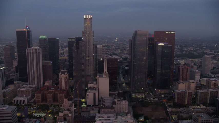 8K stock footage aerial video passing by giant skyscrapers in Downtown Los Angeles at sunrise, California Aerial Stock Footage | AX0156_060