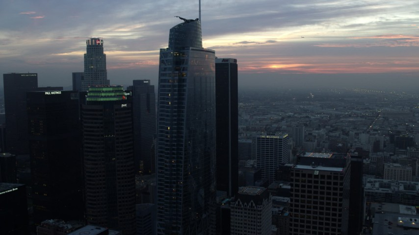 8K aerial video approaching and flying by Downtown Los Angeles, California towers and reveal city hall on a hazy morning Aerial Stock Footage | AX0156_086