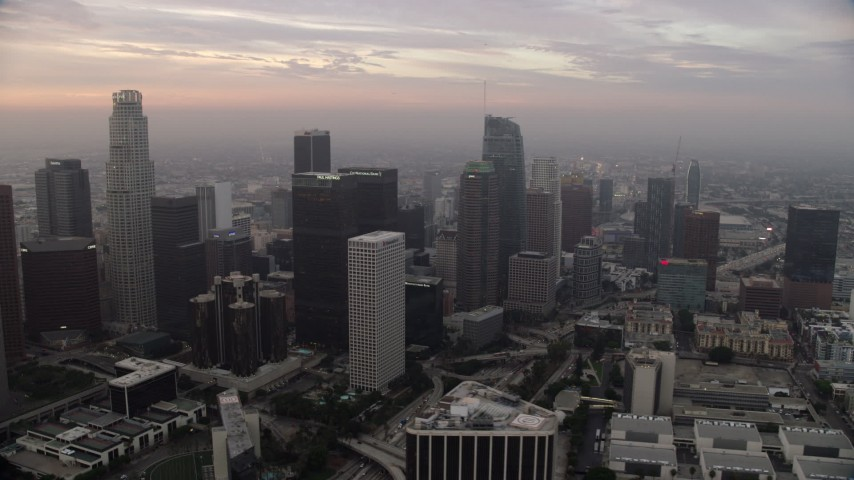 8K aerial video flying by Bank of America Plaza for a view of skyscrapers in Downtown Los Angeles, California at sunrise Aerial Stock Footage | AX0156_106
