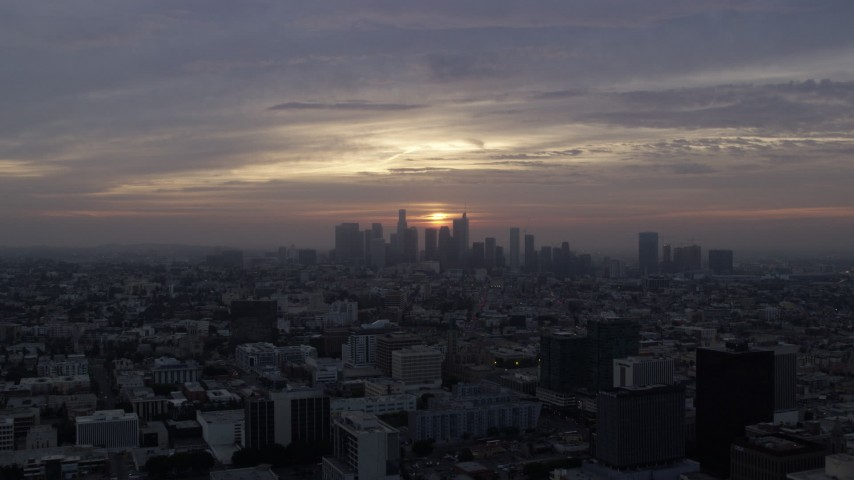 8K stock footage aerial video flying over Koreatown office buildings to approach the skyline of Downtown Los Angeles, California at sunrise Aerial Stock Footage AX0156_110 | Axiom Images