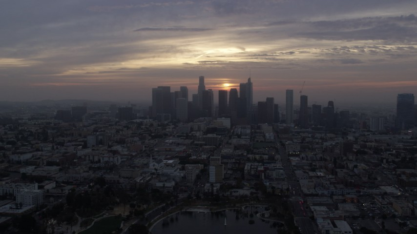 8K stock footage aerial video approaching the skyline of Downtown Los Angeles, California at sunrise, fly over MacArthur Park Aerial Stock Footage | AX0156_111