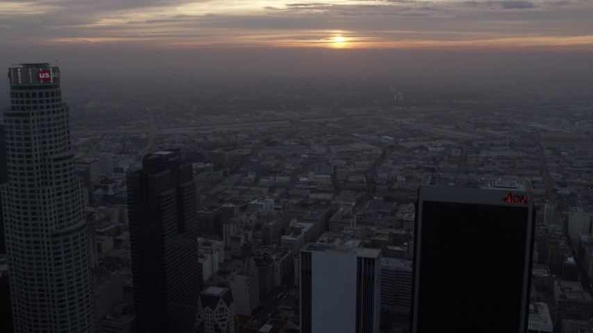 8K stock footage aerial video flying over skyscrapers in Downtown Los Angeles, California to approach the rising sun Aerial Stock Footage | AX0156_113
