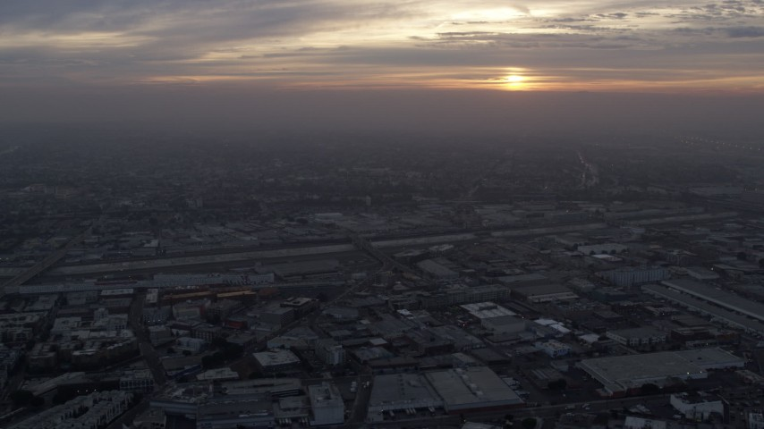 8K aerial video flying over downtown warehouse buildings to approach the LA River and Boyle Heights in Los Angeles, California at sunrise Aerial Stock Footage | AX0156_114