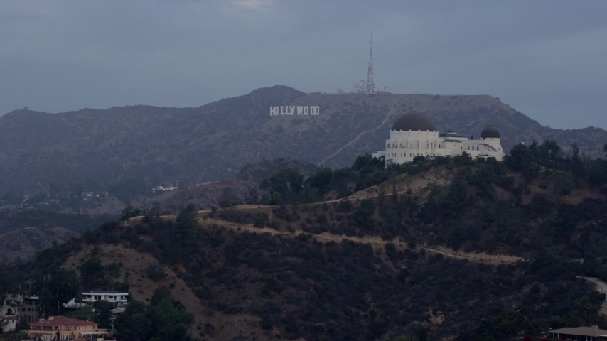 A View Of The Hollywood Sign Seen While Passing Griffith Observatory At Sunrise In Los Angeles