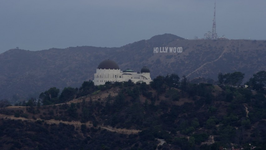 8K stock footage aerial video approaching Griffith Observatory with the Hollywood Sign in the background at sunrise, Los Angeles, California Aerial Stock Footage | AX0156_119