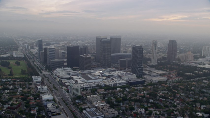 8K stock footage aerial video passing by a shopping mall set against office buildings, sunrise, Century City, California Aerial Stock Footage | AX0156_133