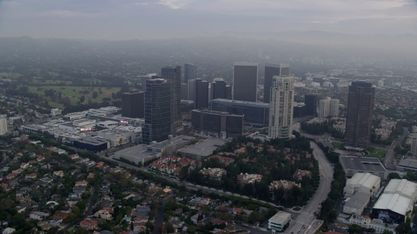 8K stock footage aerial video orbiting away from shopping mall and skyscrapers, sunrise, Century City, California Aerial Stock Footage | AX0156_134