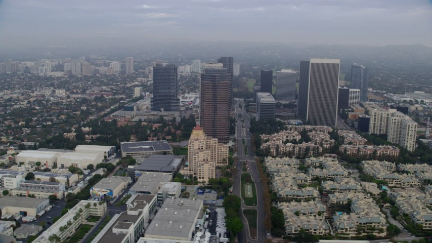 8K stock footage aerial video orbiting away from Fox Tower and skyscrapers over Avenue of the Stars, sunrise, Century City, California Aerial Stock Footage | AX0156_135