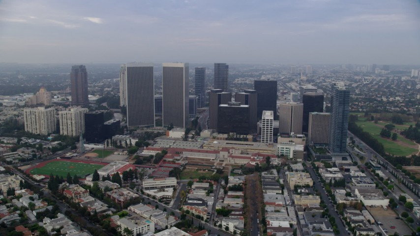 8K stock footage aerial video orbiting away from skyscrapers and Beverly Hills High School, sunrise, Century City, California Aerial Stock Footage | AX0156_137