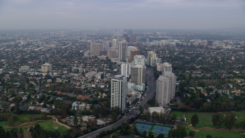 8K stock footage aerial video following Wilshire Blvd over Los Angeles Country Club and The Windmill Links, sunrise, Century City, Beverly Hills, California Aerial Stock Footage AX0156_138 | Axiom Images