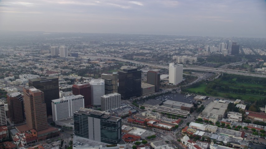 8K stock footage aerial video flying over apartment buildings following Wilshire Boulevard towards Interstate 405, sunrise, Westwood Village, California Aerial Stock Footage | AX0156_140
