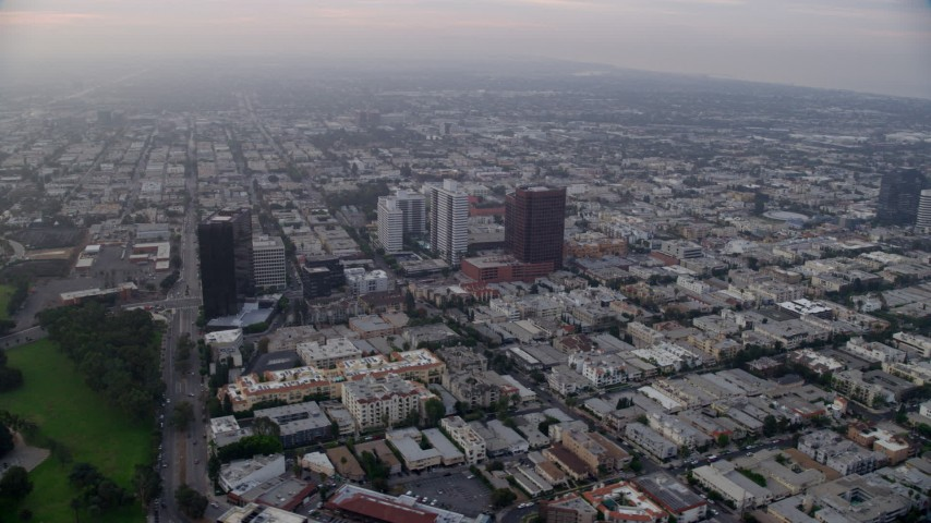 8K stock footage aerial video following Wilshire Boulevard at Federal Ave and over apartment buildings, sunrise, Sawtelle, California Aerial Stock Footage | AX0156_142