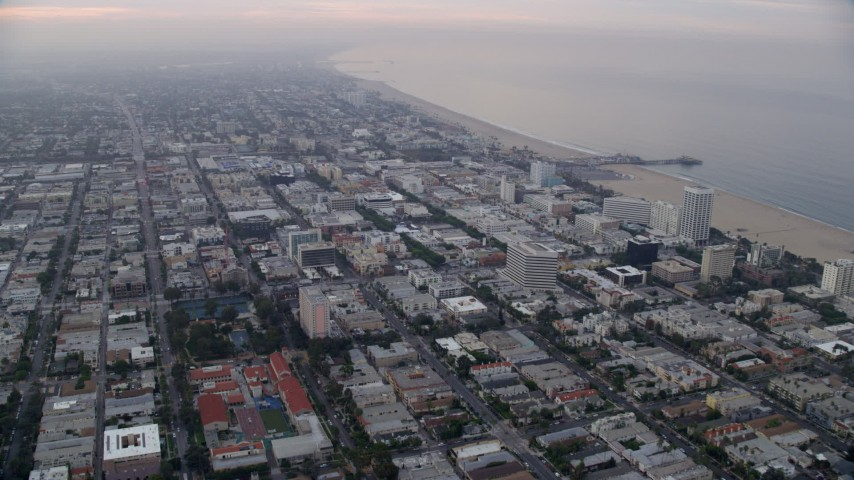 8K stock footage aerial video flying over office buildings toward Santa Monica Pier, sunrise, Santa Monica, California Aerial Stock Footage | AX0156_148