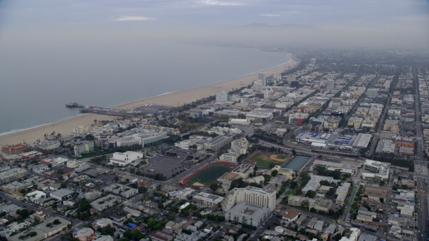 8K stock footage aerial video flying over coastal neighborhoods to approach Santa Monica Pier at sunrise, Santa Monica, California Aerial Stock Footage | AX0156_156