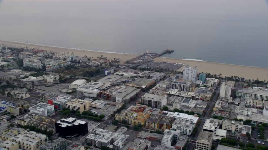 A reverse view of shops and apartment buildings in the morning near Santa Monica Pier, California Aerial Stock Footage | AX0156_158