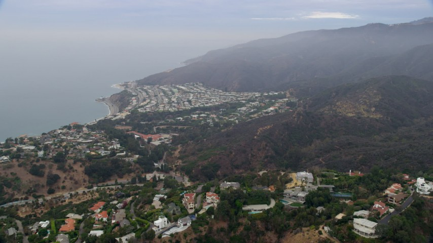8K stock footage aerial video flying over hillside mansions to approach a coastal neighborhood in the morning, Pacific Palisades, California Aerial Stock Footage | AX0156_162