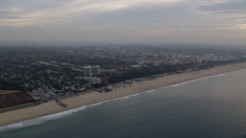 8K aerial video of light traffic on Pacific Coast Highway on the edge of Pacific Palisades / Santa Monica at sunrise, California Aerial Stock Footage | AX0156_167