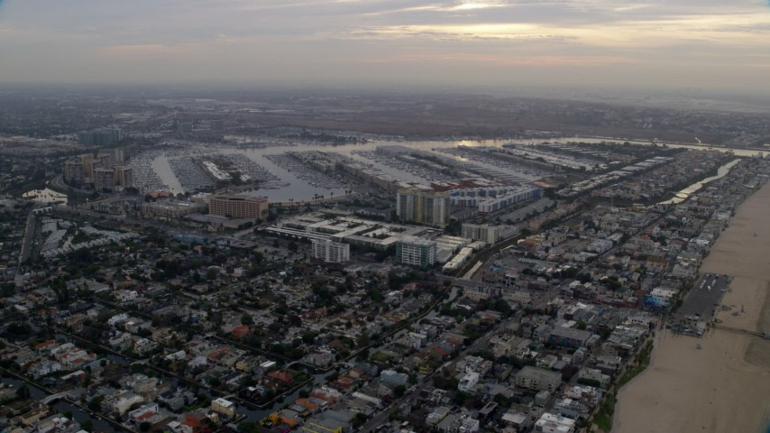 8K aerial video flying over Venice neighborhoods to approach and flyby Marina Del Rey harbor at sunrise, California Aerial Stock Footage | AX0156_172