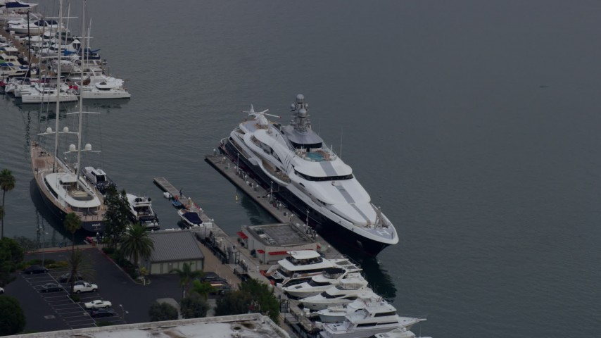 8K stock footage aerial video of a mega yacht docked in harbor with helicopter on back, sunrise, Marina Del Rey, California Aerial Stock Footage | AX0156_176