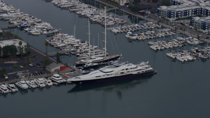 8K stock footage aerial video pulling away from a docked mega yacht with helicopter, sunrise, Marina Del Rey, California Aerial Stock Footage | AX0156_177