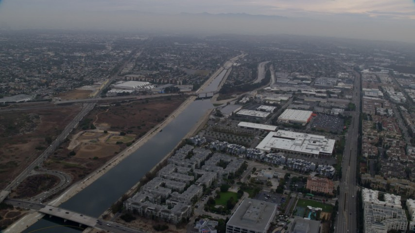 8K stock footage aerial video flying alongside the Los Angeles river canal, sunrise, Marina Del Rey, California Aerial Stock Footage | AX0156_178
