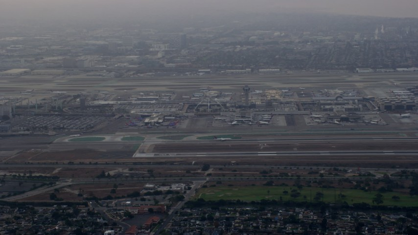 8K stock footage aerial video tracking an airplane landing at LAX amongst thick cloud coverage, sunrise, Los Angeles, California Aerial Stock Footage | AX0156_180
