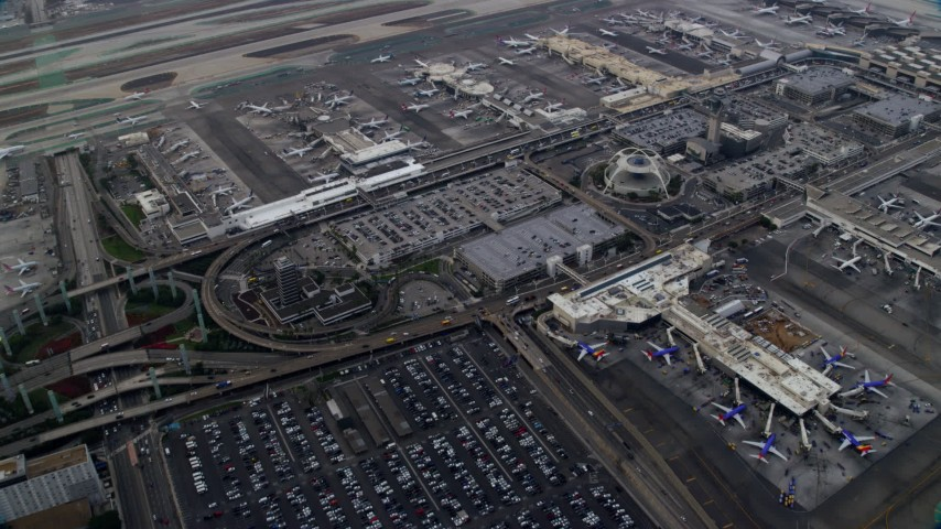 8K stock footage aerial video flying over LAX and parked airplanes, sunrise, Los Angeles, California Aerial Stock Footage | AX0156_181