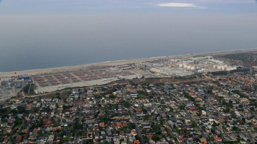 8K stock footage aerial video flying over coastal community towards Dockweiler beach and water treatment plant, sunrise, El Segundo, California Aerial Stock Footage | AX0156_186