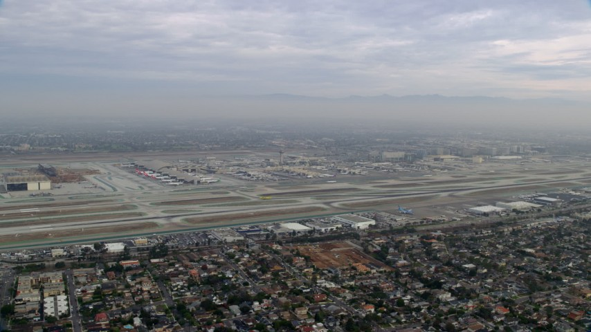 8K stock footage aerial video of a sideview of LAX on a cloudy morning, sunrise, Los Angeles, California Aerial Stock Footage | AX0156_189