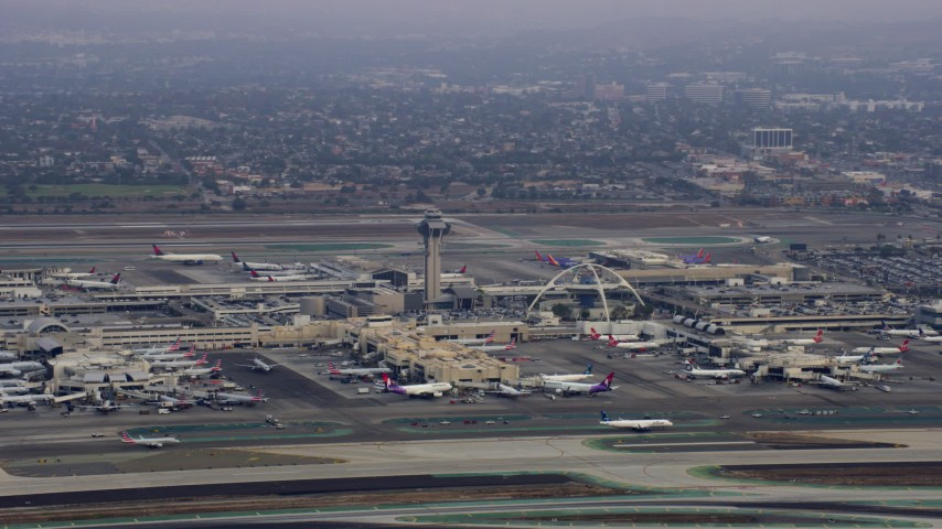 8K stock footage aerial video of LAX and its control tower on a cloudy morning, sunrise, Los Angeles, California Aerial Stock Footage AX0156_190 | Axiom Images
